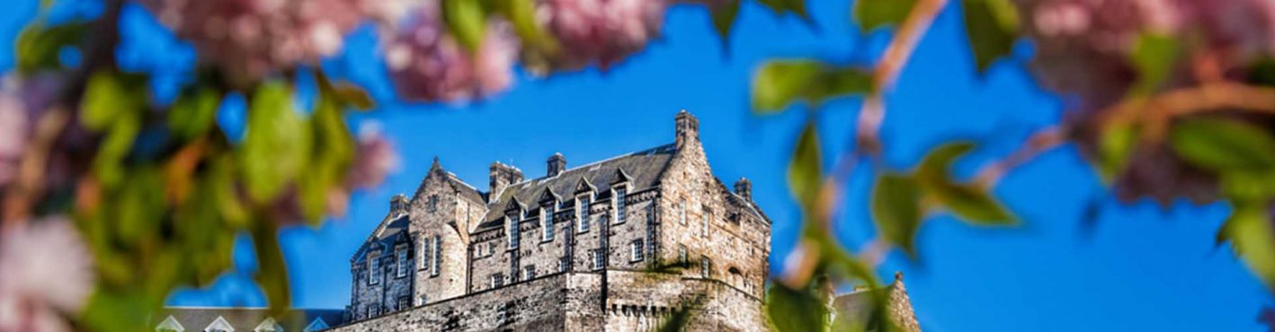 Spring trees framing Edinburgh Castle